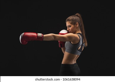 Side view of a gorgeous young woman with boxing gloves, standing in position, ready to fight, copy space. Studio shot on black background, low key. Kickboxing and fight sport concept
