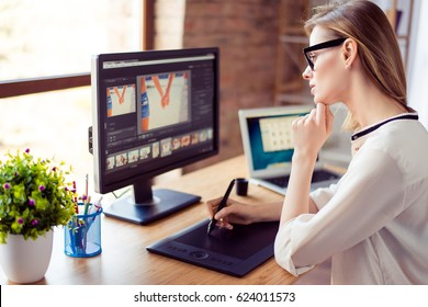 Side view of graphic designer working with interactive pen display, digital drawing tablet and pen on a computer in workstation