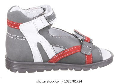 Side view of gray, red and white suede boy sandal with two velcros and slits and slots, isolated on white