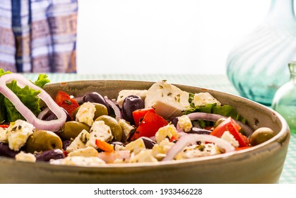 Side view Greek salad with onions, olives, feta cheese, pickle, lettuce, tomato, in ceramic bowl, on a green and white checkered tablecloth. Wine glasses. Wine decanter. Rear window slatted curtain