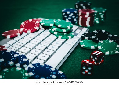 Side view of a green poker table with some poker cards on a white keyboard. Addicted to poker online concept.
