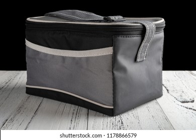 side view grey and black lunch pack carrier on a wood table on black background
