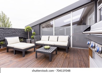 Side view of grill on stylish terrace with wooden board floor and bright garden furniture