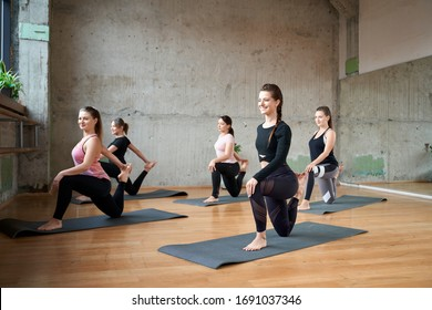 Side view of group of attractive sport girls doing Horse rider exercise, anjaneyasana pose in fitness hall. Young fit women stretching on mats in spacy gym with big mirror. Loft interior.