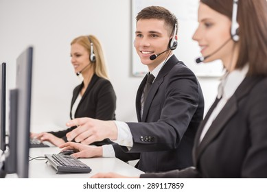 Side view of a group of business colleagues with headsets using computers at office desk.