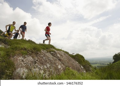 Side view of a group of people running on hill