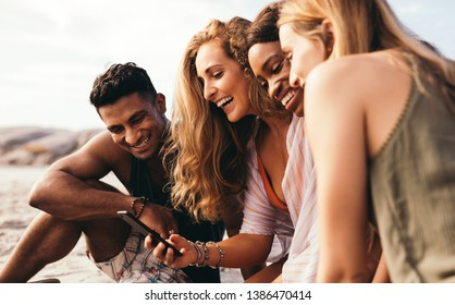 Side view of a group of smiling friends sitting outdoors looking at a mobile phone. Cheerful friends on vacation having fun sitting on beach taking a selfie on mobile phone.