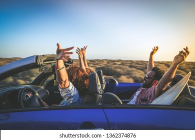 Side view group three euphoric friends in convertible car twisting and waving Two curly girls and charming bearded man on vacation having fun in topless auto Arms up palms open driving in the sunlight