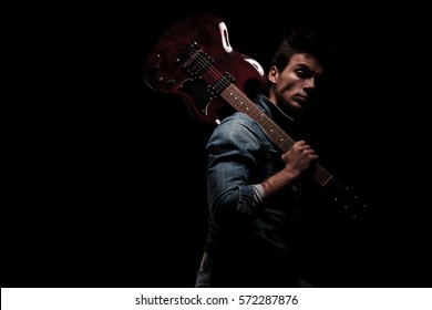 side view of a guitarist holding his guitar on shoulder and looks at the camera on black background