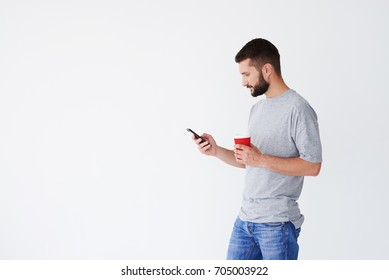 Side view of guy holding cup of coffee and Smartphone, looking seriously, having black beard, mid shot