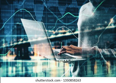 Side view of hacker using laptop with forex chart on blurry night city background. Hacking and trade concept. Double exposure