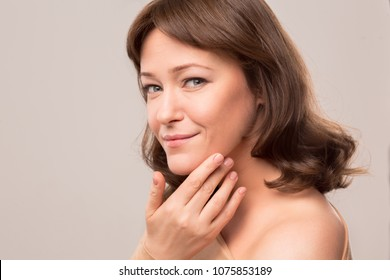 Side view half length image of lightly smiling brunette.Isolated on white background. Mid age woman over 35 years old beauty concept.