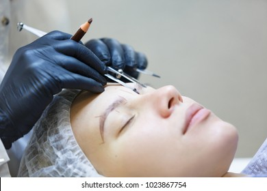 Side view of the hand of the master cosmetologist measures the proportions of the eyebrows with special tool for applying the paint. Concept of microblading
