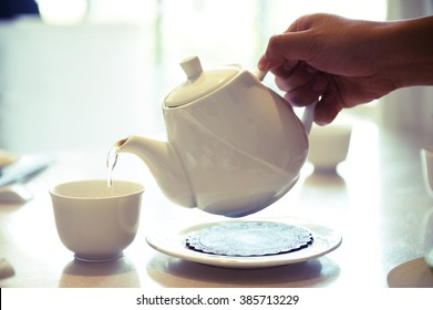 Side view of a hand pouring Chinese tea in tea cup.