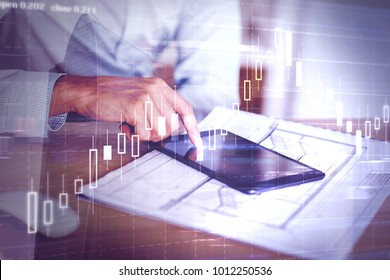 Side view of hand using tablet at desk with architectural sketch and forex chart. Analysis and market concept. Double exposure