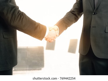 Side view of handshake on abstract blurry bright office background. Teamwork and union concept