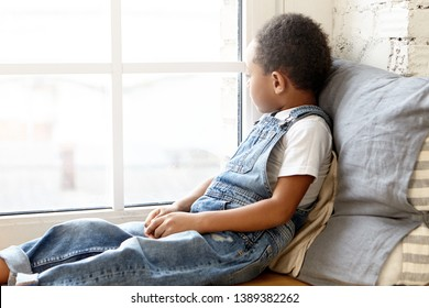 Side view of handsome adorable skinny dark skinned preschooler dressed in stylish clothes sitting on wooden windowsill, leaning on pillow, looking outside, having bored or lonely day at home