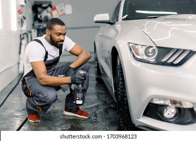 Side view of handsome African American male car wash worker hodling in hand special chemical cleaner solution and spraying it on car wheel rim. Car wash and detailing concept