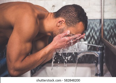 Side view of handsome Afro American man washing himself in bathroom