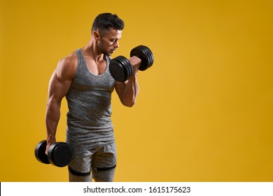 Side view of handsome athletic bodybuilder lifting heavy weight. Strong brutal guy in sportswear pumping up muscles. Isolated on yellow studio background with copy space. Concept of sport.