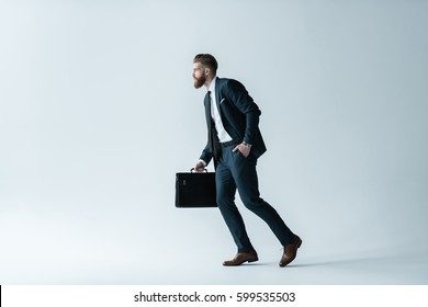Side view of handsome bearded businessman running with briefcase isolated on grey