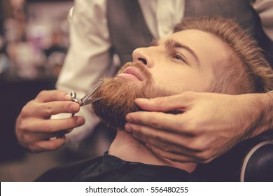 Side view of handsome bearded man having his beard cut by hairdresser at the barbershop