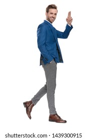 Side view of handsome casual guy greeting and holding his hand in his pocket while stepping and wearing an elegant suit on white studio background
