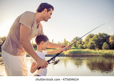 Side view of handsome father and his little son smiling while catching fish in the pond using a fishing rod