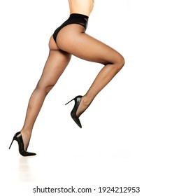 Side view of a handsome female legs in black fish net tights and high heels on a white background