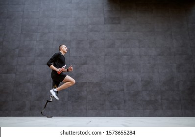Side view of handsome fit caucasian sportsman with artificial leg running outside.