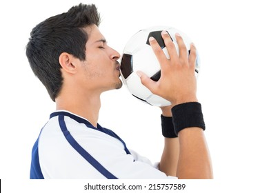 Side view of a handsome football player kissing ball over white background