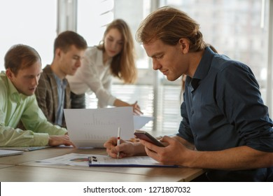 Side view of handsome male worker sitting at table, looking at papers and calculating data on phone. Smart man working in office and checking information. Concept of business and job.