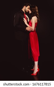 Side view of handsome man embracing beautiful girlfriend in red dress isolated on black
