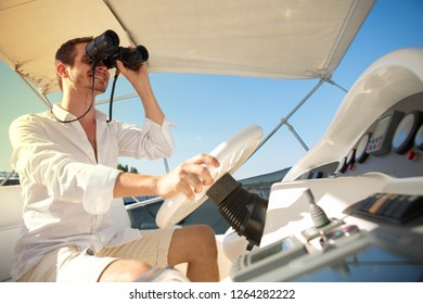 Side view of handsome man managing steering wheel of yacht and smiling. He wearing white clothes and holding binaculars in hands. Concept of sail boating, voyage and marina.