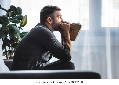 side view of handsome man with panic attack breathing in paper bag in apartment