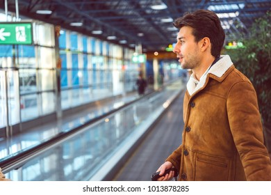 Side view of handsome man standing on travelator in airport.