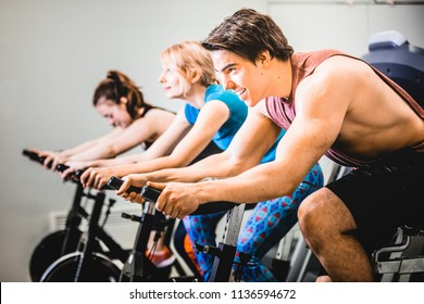 Side view of handsome man starting cycle training on bicycle working out in gym with other people.