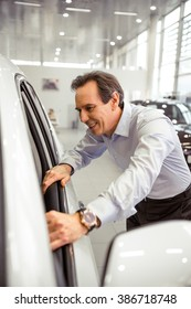 Side view of handsome middle aged businessman is smiling while looking at car interior