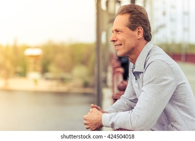 Side view of handsome middle aged man in sports uniform leaning on bridge and smiling while having break during morning run