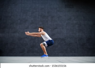 Side view of handsome muscular caucasian man in shorts and t-shirt doing squatting exercise outdoors. In background is gray wall.