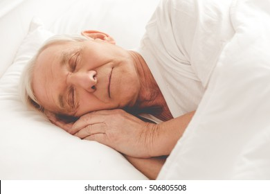 Side view of handsome old man sleeping in bed