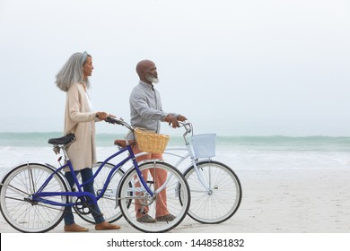 Side view of handsome senior African-American couple walking with bicycles on the beach with his hands in pockets on beautiful day. Authentic Senior Retired Life Concept