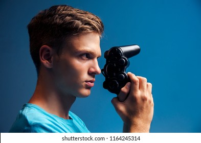 Side view handsome teen holding video game controller like a gun