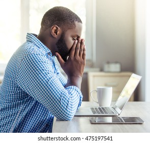 Side view of handsome tired Afro American businessman in casual clothes leaning on his hands while working with a laptop at home