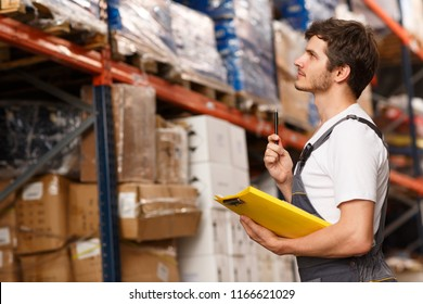 Side view of handsome worker concentrated on goods, standing near shelves in warehouse. Man holding pen and yellow clipboard. Specialist wearing white t shirt and uniform.