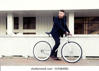 Side view of handsome young bearded man looking away while riding on his bicycle outdoors. stylish businessman going to work by bike