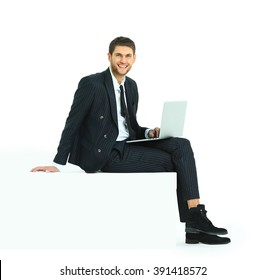 Side view of a handsome young business man sitting on a white modern chair