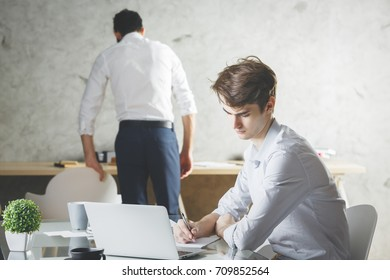 Side view of handsome young businessman using laptop in modern office with blurry colleague in the background. Project concept