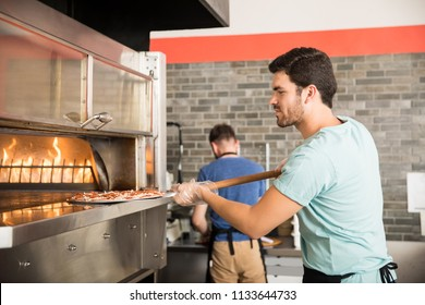 Side view of handsome young chef using peel to put pizza in oven for baking