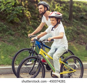 Side view of handsome young dad and his cute little son in casual clothes and helmets looking forward and smiling while riding bikes in park